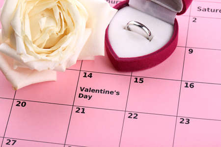 Notes on the calendar (valentines day) and wedding ring, close-up photo