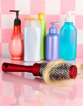 comb brush with hair and cosmetic bottles in bathroom Stock Photo - 17291800