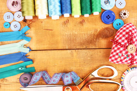 craft work: Sewing accessories and fabric on wooden table close-up Stock Photo
