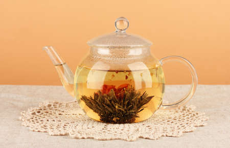Exotic green tea with flowers in glass teapot on table on color background.Process of making tea photo
