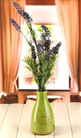 Decorative ceramic vase with lavender on wooden table on window background photo