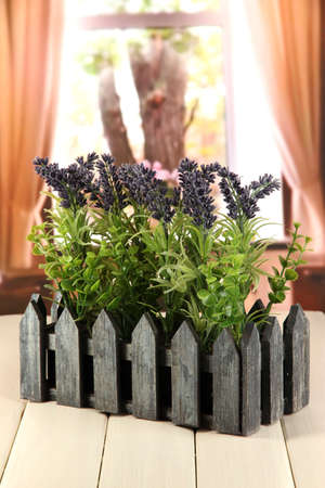 Decorative lavender in wooden box on wooden table on window background photo