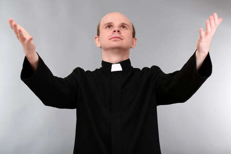 Young priest on gray background photo