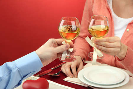 hands of romantic couple toasting their wine glasses over a restaurant table Stock Photo - 17292119