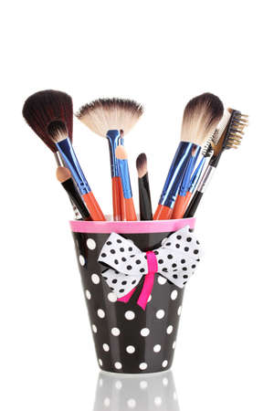 Makeup brushes in a black polka-dot cup isolated on white photo