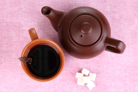 Top view of cup of tea and teapot on pink tablecloths photo