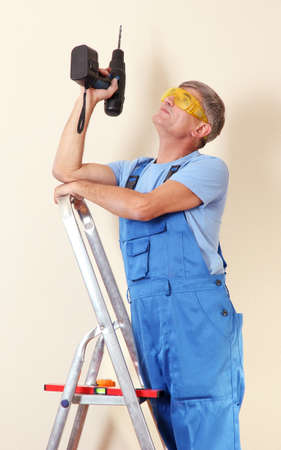 Handyman drill standing on ladder close-up photo