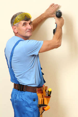 Handyman drill wall close-up photo