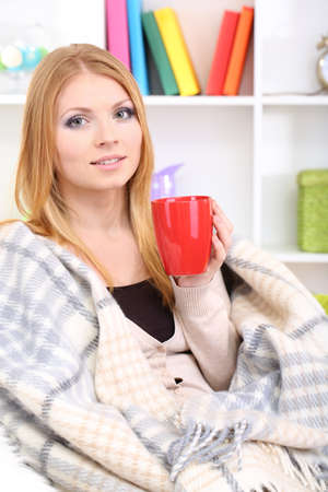 Attractive young woman sitting on sofa, holding cup with hot drink, on home interior background Stock Photo - 17544470