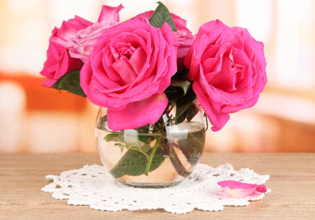 Beautiful pink roses in vase on wooden table on room background Stock Photo - 17362709