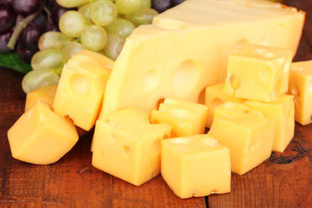 Cut cheese with grape on wooden table photo