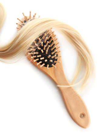 wooden comb brush with hair, isolated on white photo
