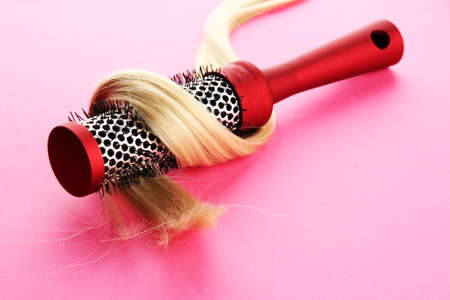 comb brush with hair,  on pink background photo