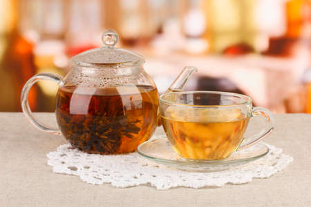Exotic green tea with flowers in glass teapot on bright background Stock Photo - 17362833