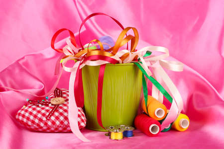 Color bucket with multicolor ribbons and thread on pink fabric background Stock Photo - 17348243