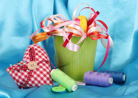 Color bucket with multicolor ribbons and thread on blue fabric background photo