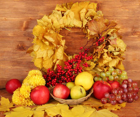 Autumnal composition with yellow leaves, apples and mushrooms on wooden background Stock Photo - 17348235