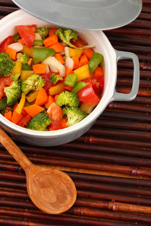 Vegetable stew in gray pot on bamboo mat background photo