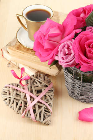 Beautiful pink roses in vase on wooden table close-up photo