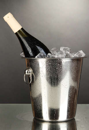 Bottle of wine in ice bucket on black background photo