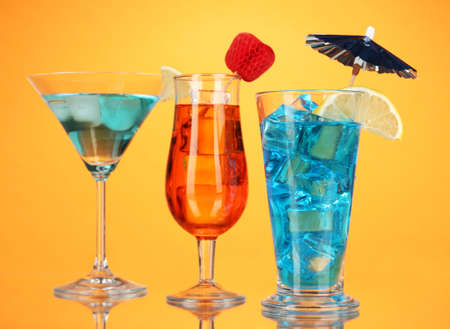 Alcoholic cocktails with ice on orange background photo