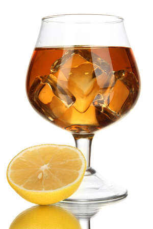 Glass of brandy with ice and lemon isolated on white photo