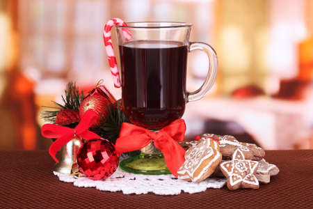 Hot tasty drink with christmas candy and other decorations on bright background photo