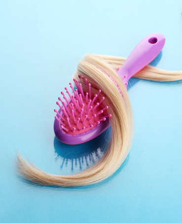comb brush with hair,  on blue background Stock Photo - 17348504
