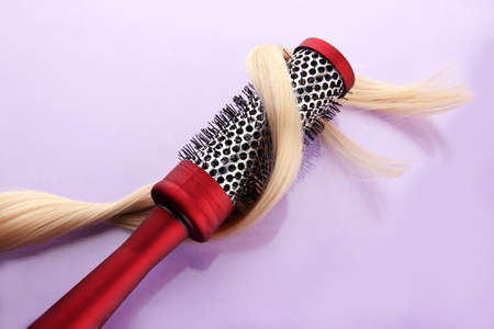 comb brush with hair,  on purple background Stock Photo - 17348428