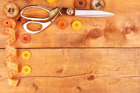 Accessori da cucire e tessuto su tavola di legno close-up Archivio Fotografico