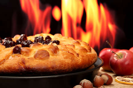 tasty homemade pie with jam, on wooden table on flame background photo