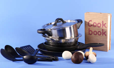 composition of kitchen tools and cook book on blue background photo