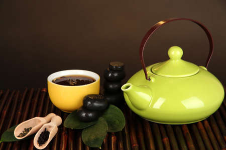 Chinese tea ceremony on bamboo table on brown background photo
