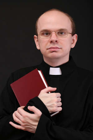 Young pastor with Bible, isolated on black