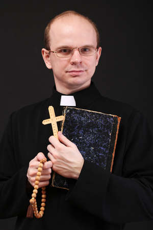 reverent: Young pastor with wooden cross and Bible, isolated on black
