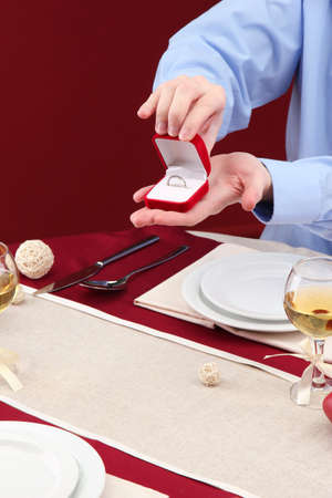 A man proposing and holding up an engagement ring over restaurant table photo