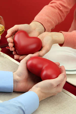 hands of romantic couple with hearts over a restaurant table Stock Photo - 17348247