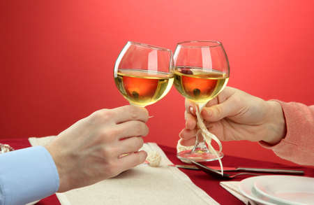 hands of romantic couple toasting their wine glasses over a restaurant table photo