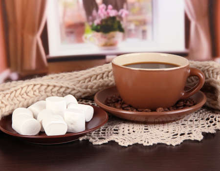 cup of coffee with scarf on table in room photo