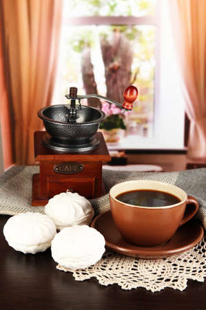 cup of coffee with scarf and coffee mill on table in room photo