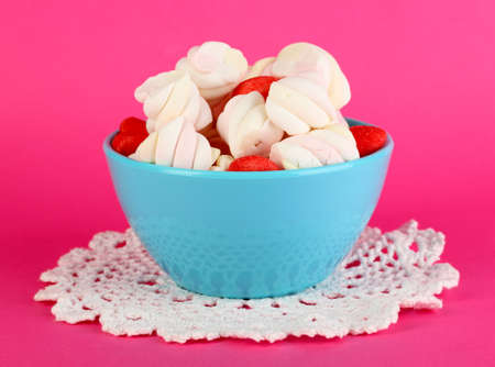 Gentle marshmallow in bowl on pink background photo