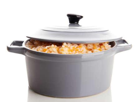 Taste rice porridge with pumpkin in saucepan, isolated on white  photo