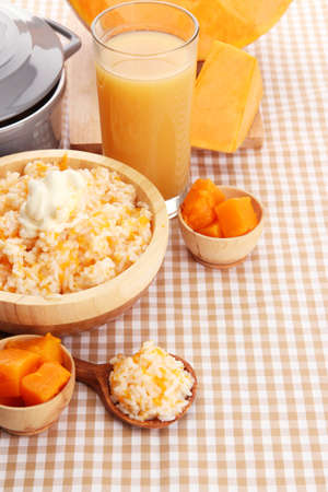 Taste rice porridge with pumpkin and glass of juice on tablecloth background  photo