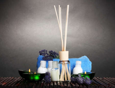 air freshener, bottles, towel and candles on bamboo mat on gray background photo