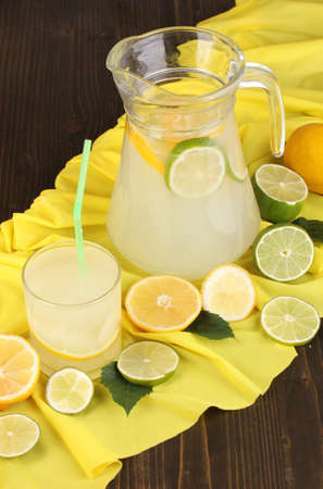 Citrus lemonade in glass and pitcher of citrus around on yellow fabric on wooden table close-up Stock Photo - 17399603