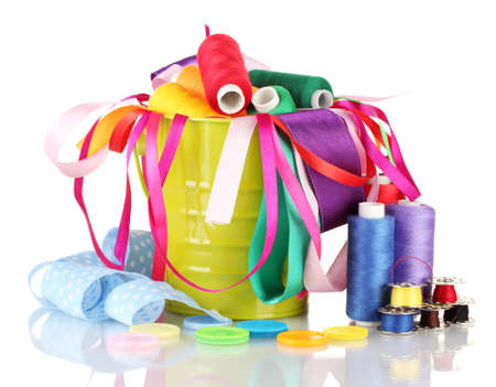 Color bucket with multicolor ribbons and thread isolated on white photo