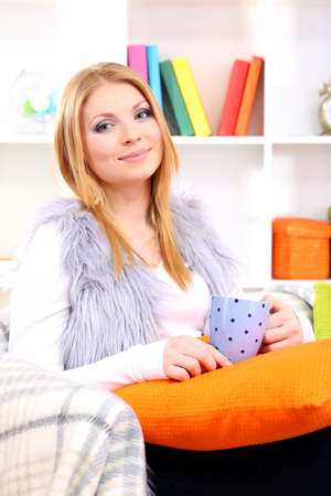 Attractive young woman sitting on sofa, holding cup with hot drink, on home interior background Stock Photo - 17544489