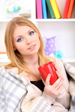 Attractive young woman sitting on sofa, holding cup with hot drink, on home interior background Stock Photo - 17544494
