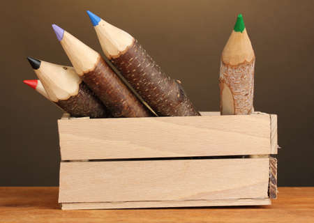 Colorful wooden pencils in box on brown background photo