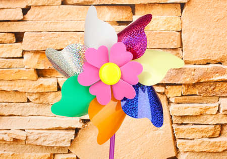Colored pinwheel on stone wall background photo